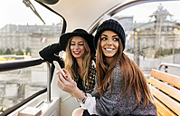 France, Paris, two smiling women with cell phone on a tour bus - MGOF02629