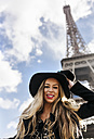 France, Paris, portrait of smiling woman in front of Eiffel Tower - MGOF02635