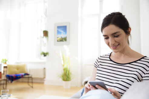 Smiling woman at home looking on cell phone - FKF02077