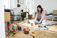 Woman at home sitting on floor using laptop surrounded by toys - FKF02092