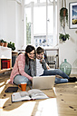 Mother and daughter at home sitting on floor using laptop - FKF02095