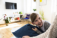 Happy daughter looking at mother at home - FKF02104