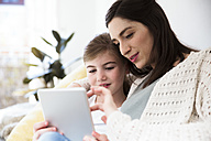 Smiling mother and daughter at home using tablet - FKF02107