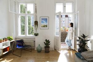 Woman at home standing at balcony door - FKF02113