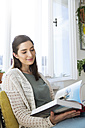 Smiling woman at home sitting on chair reading book - FKF02122