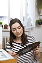 Woman at home looking at record - FKF02125