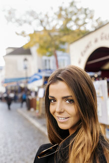 France, Paris, portrait of smiling young woman in Montmartre - MGOF02648