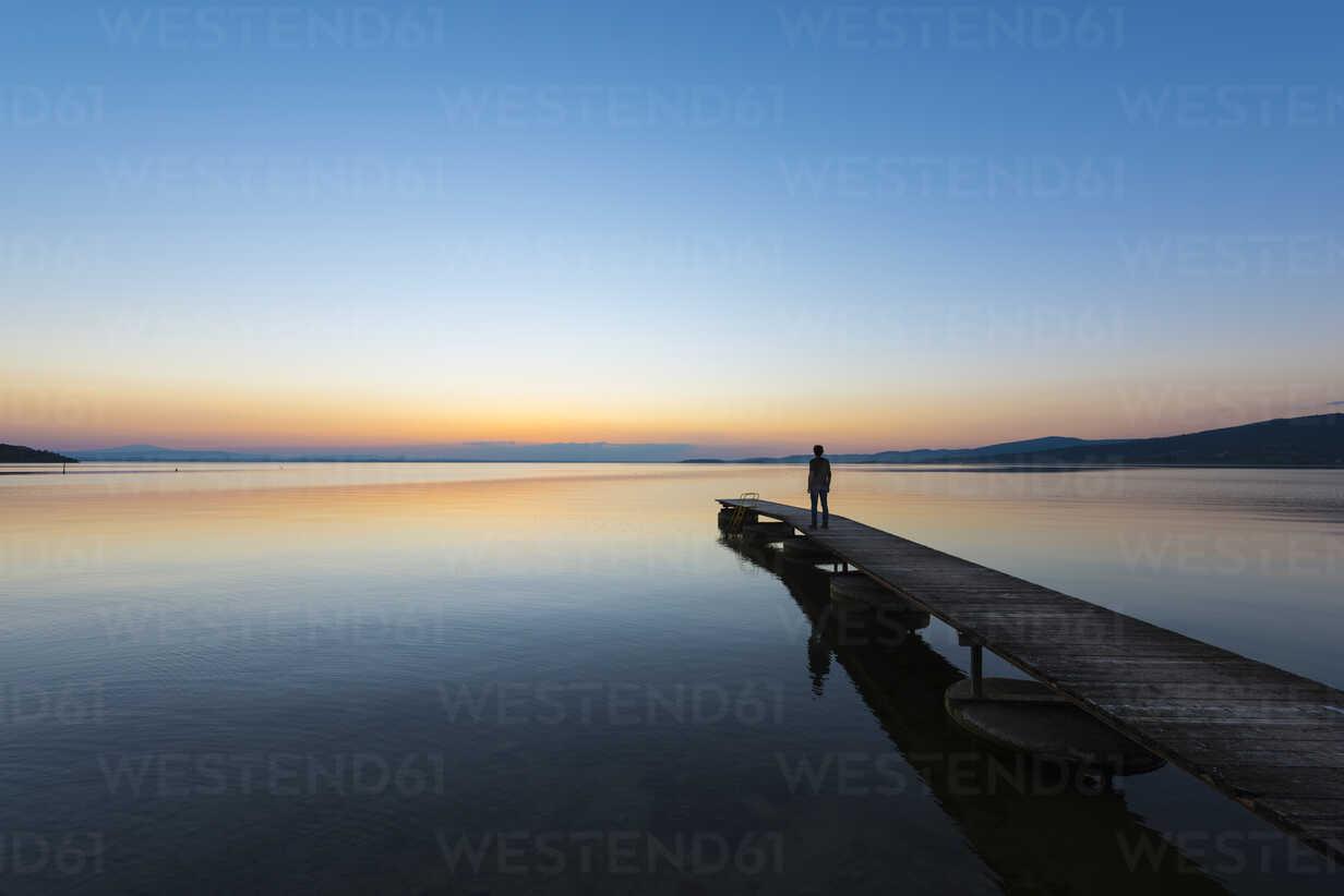 Italy, Umbria, Lake Trasimeno, silhouette of man standing on jetty watching sunset - LOMF00451 - Lorenzo Mattei/Westend61