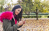Young woman looking on cell phone in a park in autumn - MGOF02652