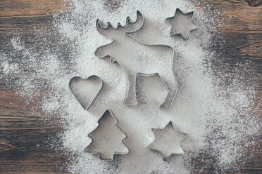 Five cookie cutters sprinkled with flour on wood - RTBF00539