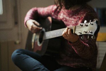 Young woman playing guitar at home - KKAF00156