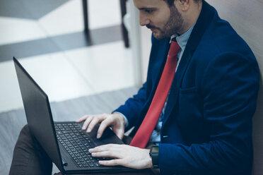 Businessmann using laptop in office - ZEDF00446