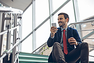 Smiling businessmann sitting on stairs using cell phone - ZEDF00449