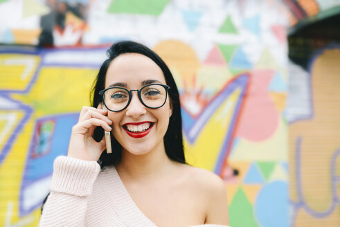Portrait of happy woman on the phone in front of graffiti wall - GEMF01292