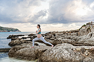 Pregnant woman practising yoga at the sea - DIGF01458