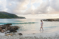 Pregnant woman walking on the beach - DIGF01467