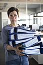 Businesswoman in office holding folders - RBF05233