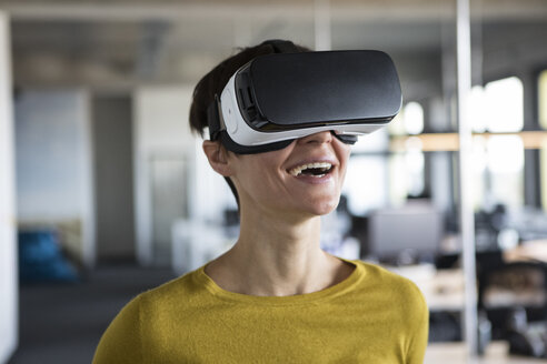 Happy woman in office wearing virtual reality glasses - RBF05239
