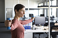 Businesswoman in office exercising with dumbbells - RBF05245