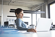 Businesswoman in office with laptop thinking - RBF05260