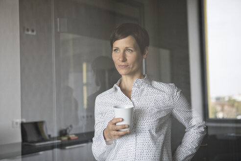 Smiling woman with cup of coffee looking out of window - RBF05272