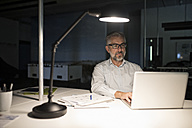Businessman in office using laptop in the dark - RBF05278