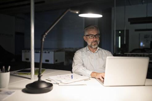 Businessman in office using laptop in the dark - RBF05278