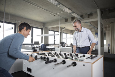 Two colleagues playing foosball in office - RBF05284