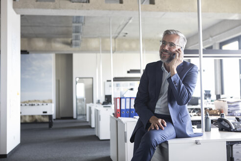 Businessman in office talking on cell phone - RBF05296