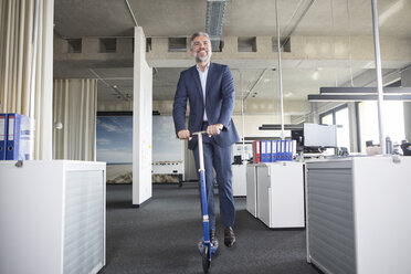 Businessman on scooter in office - RBF05302