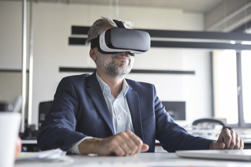 Businessman in office wearing virtual reality glasses - RBF05308