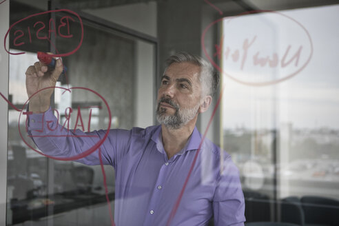 Businessman in office writing on glass wall - RBF05332