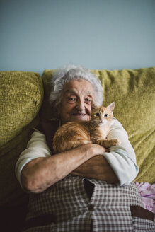 Portrait of happy senior woman cuddling with her cat on the couch - RAEF01593