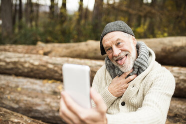Portrait of senior man pulling funny faces while taking selfie - HAPF01160