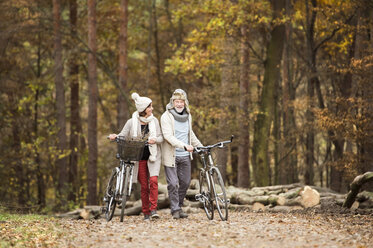 Senior couple with bicycles in autumnal wood - HAPF01166