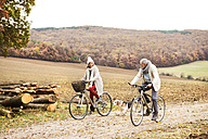 Senior couple doing a bicycle trip with dog in autumn - HAPF01169