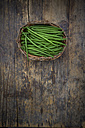 Wickerbasket of green beans on dark wood - LVF05641