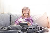 Portrait of little girl sitting on couch using tablet - LVF05649