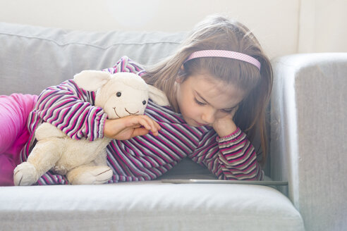 Little girl lying on couch with soft toy using tablet - LVF05652