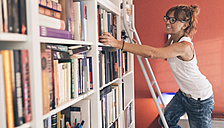 Woman taking a book from bookshelf - MGOF02674