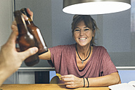 Smiling woman clinking beer bottle - MGOF02683