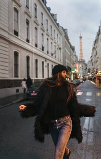 France, Paris, young woman on the street with the Eiffel Tower in the background - MGOF02688
