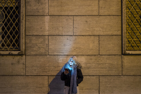 Young woman leaning against facade at night looking at her smartphone - SIPF01145