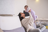 Mother holding up baby girl at home - SIPF01151