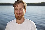 Smiling young man at a lake - FMKF03278