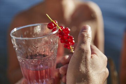 Hand holding a drink with red currants - FMKF03284