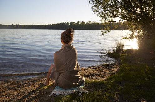 Young woman sitting at a lake at sunset - FMKF03290