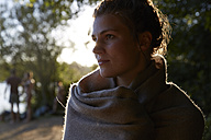Young woman wrapped in a blanket at sunset - FMKF03293