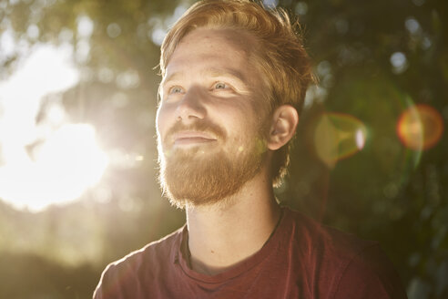 Smiling young man in backlight outdoors - FMKF03296