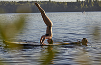 Woman doing a handstand on a paddleboard in a lake - FMKF03305